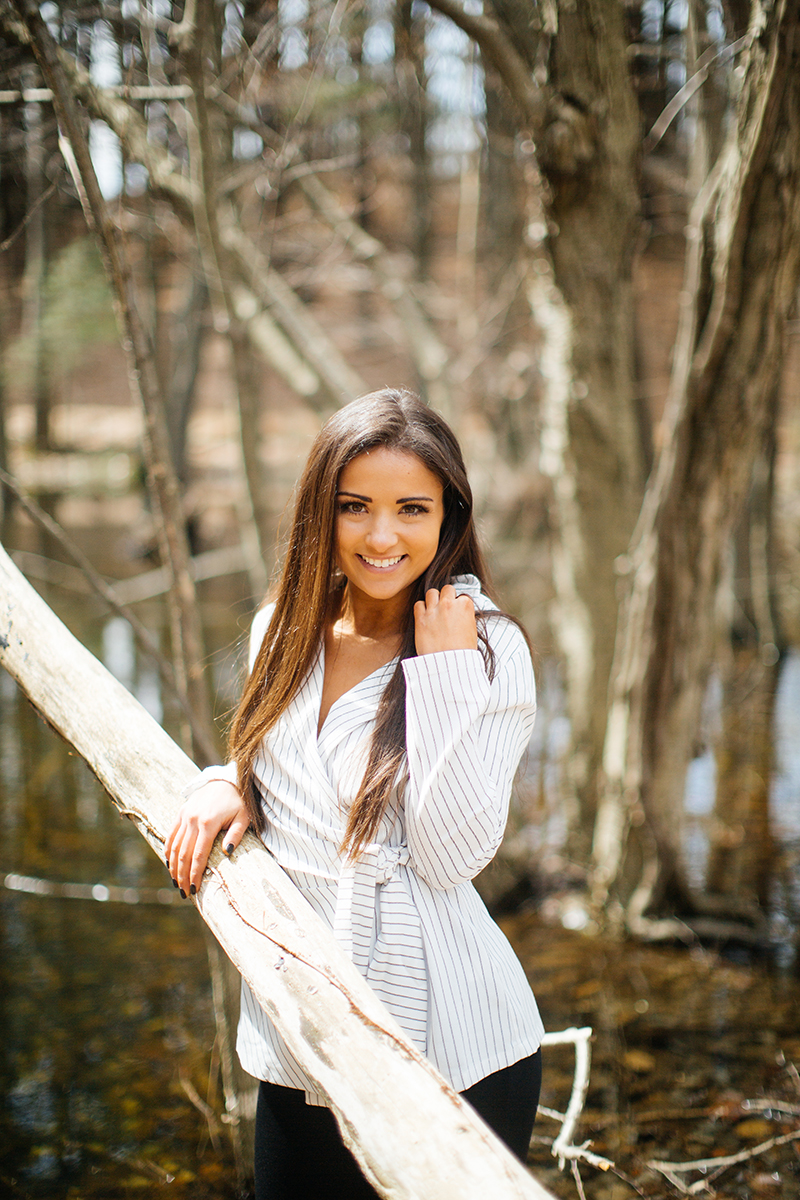 A beautiful young brunette poses for a Blue Hills Reservation boudoir photography session wearing a striped white button up shirt and black shorts leaning against a tree near a pond in the woods near Milton, Massachusetts