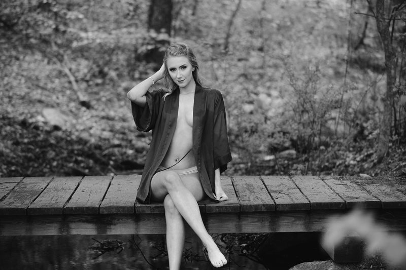 A beautiful young blonde woman posing topless for an Ashland Park boudoir photography session wearing a red silk robe and white underwear sitting on a wood bridge over a creek in the woods near Boston, Massachusetts