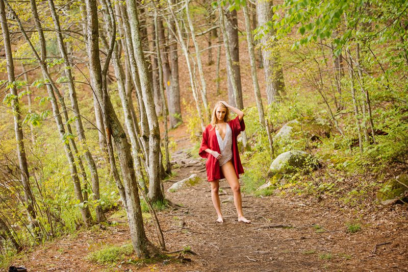 A beautiful young blonde woman posing topless for an Ashland Park boudoir photography session wearing a red silk robe and white lingerie standing on a trail in the woods near Boston, Massachusetts