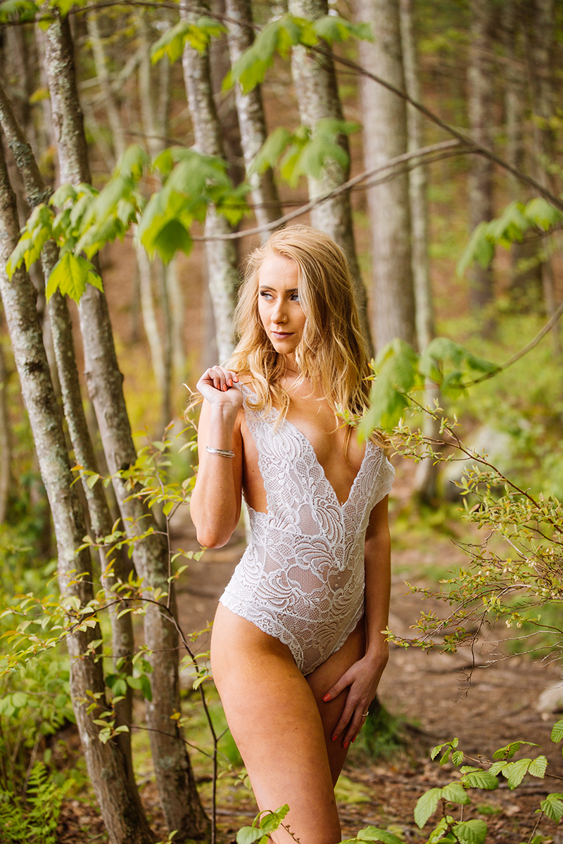 A beautiful young blonde woman posing topless for an Ashland Park boudoir photography session wearing white lingerie standing on a trail in the woods near Boston, Massachusetts