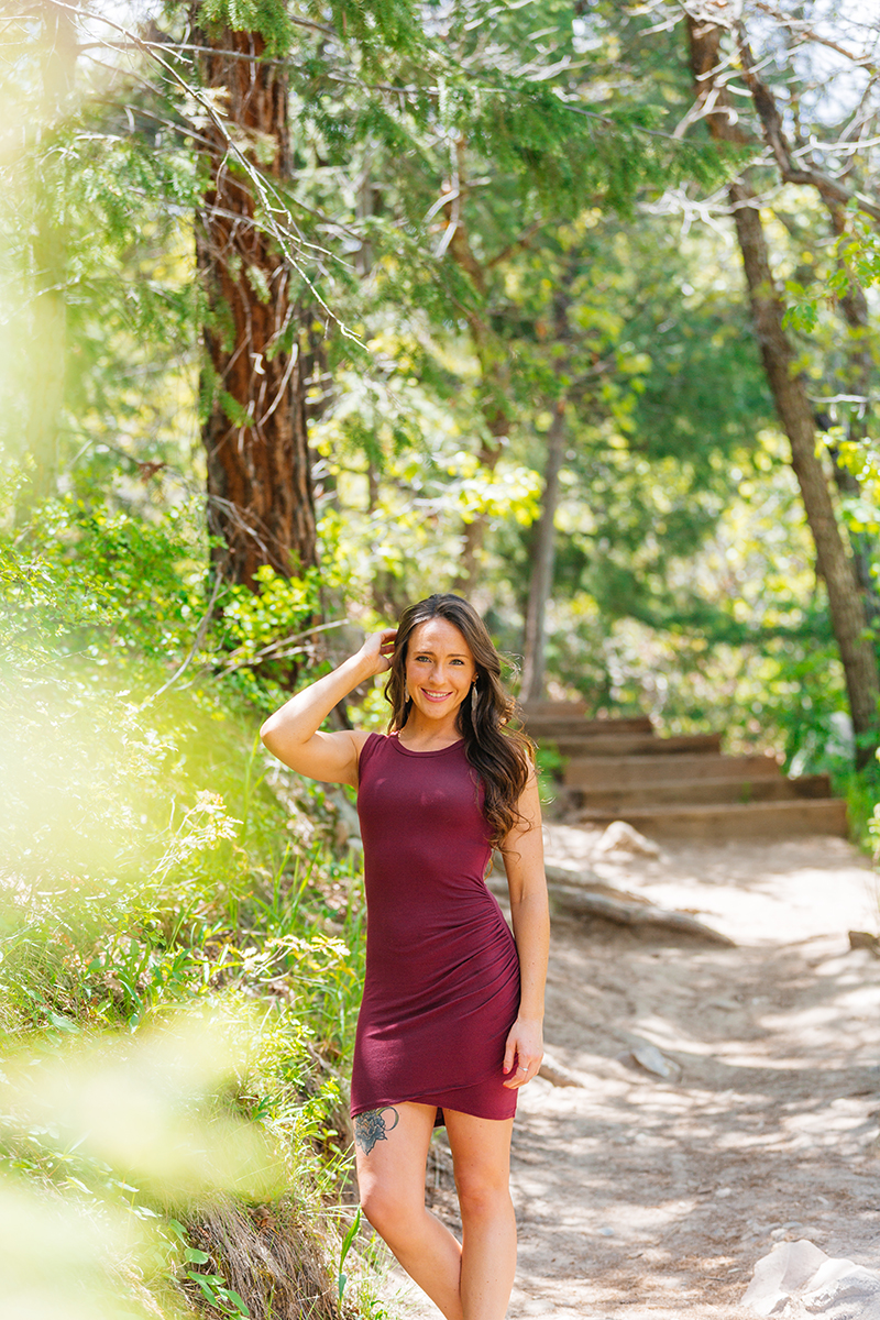 A beautiful young brunette woman poses for a Castlewood Canyon boudoir photography session wearing a burgundy dress on a trail surrounded by trees in Castle Rock, Colorado