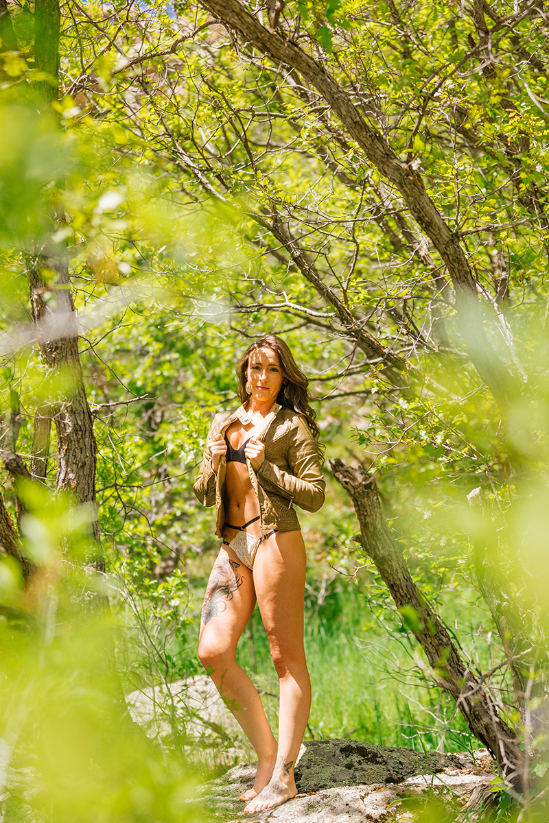 A beautiful young brunette woman poses for a Castlewood Canyon boudoir photography session wearing a tan leather jacket, a black bra and black underwear standing in a forested area in Castle Rock, Colorado