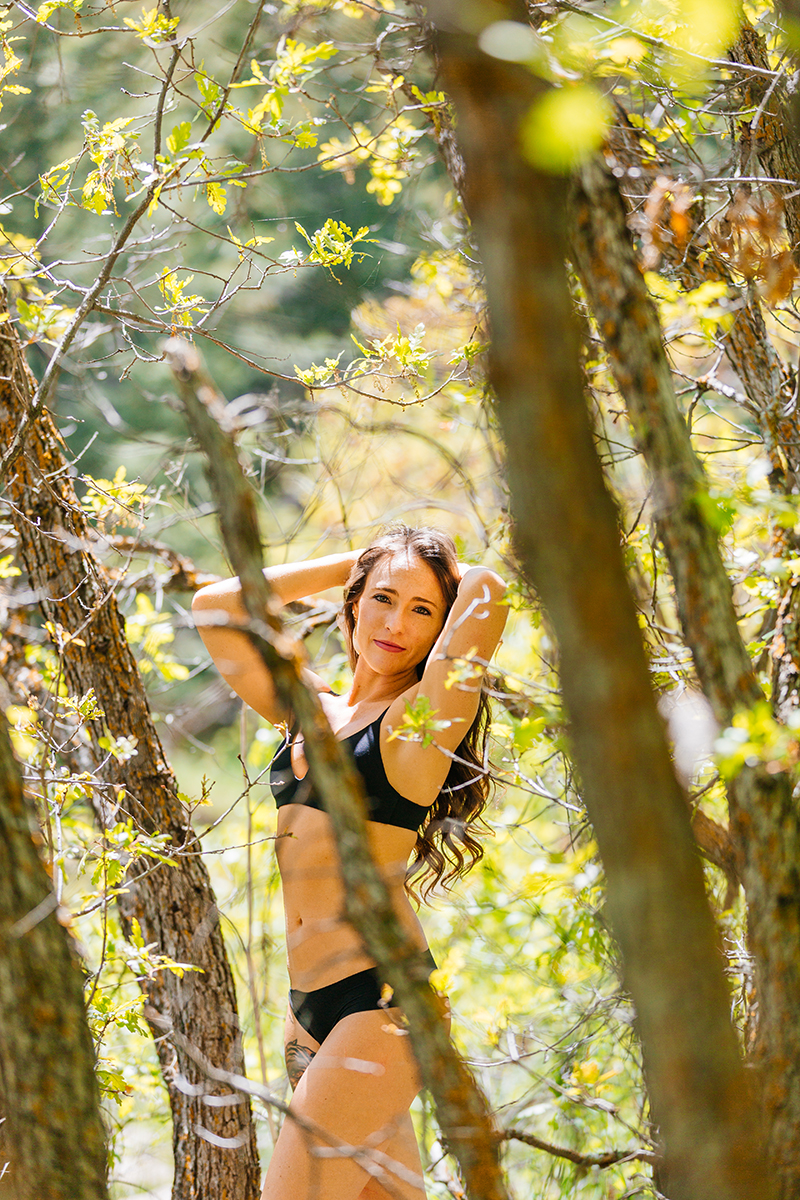 A beautiful young brunette woman poses for a Castlewood Canyon boudoir photography session wearing a black bra and underwear set standing in a forested area in Castle Rock, Colorado