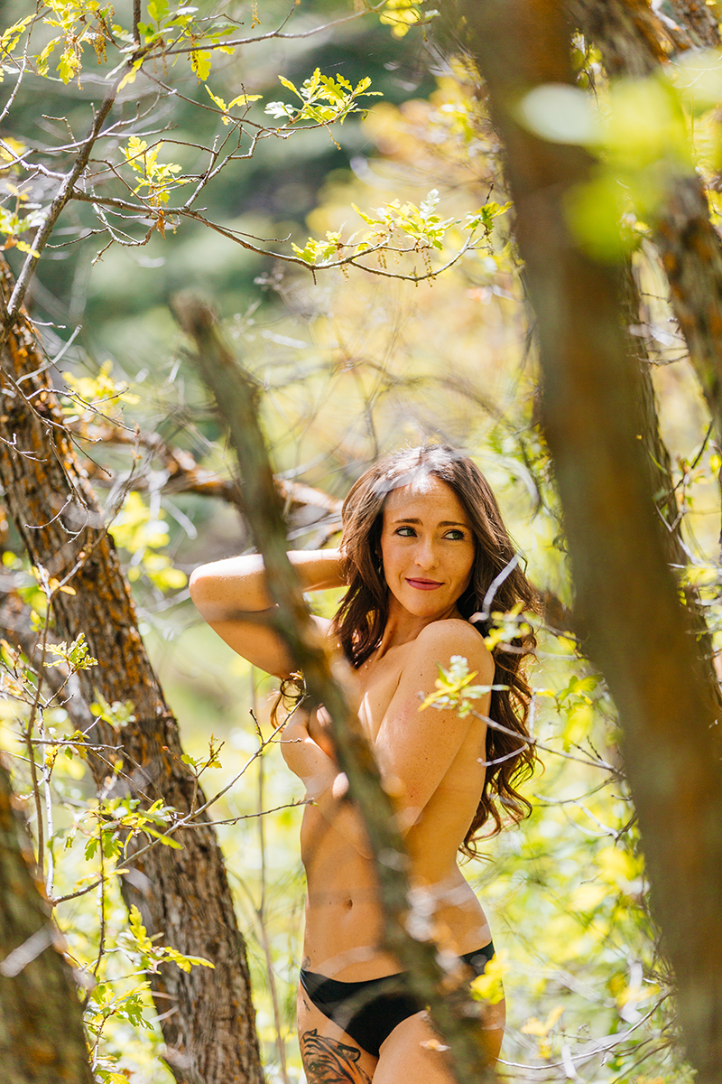 A beautiful young brunette woman poses topless for a Castlewood Canyon boudoir photography session wearing black underwear standing in a forested area in Castle Rock, Colorado