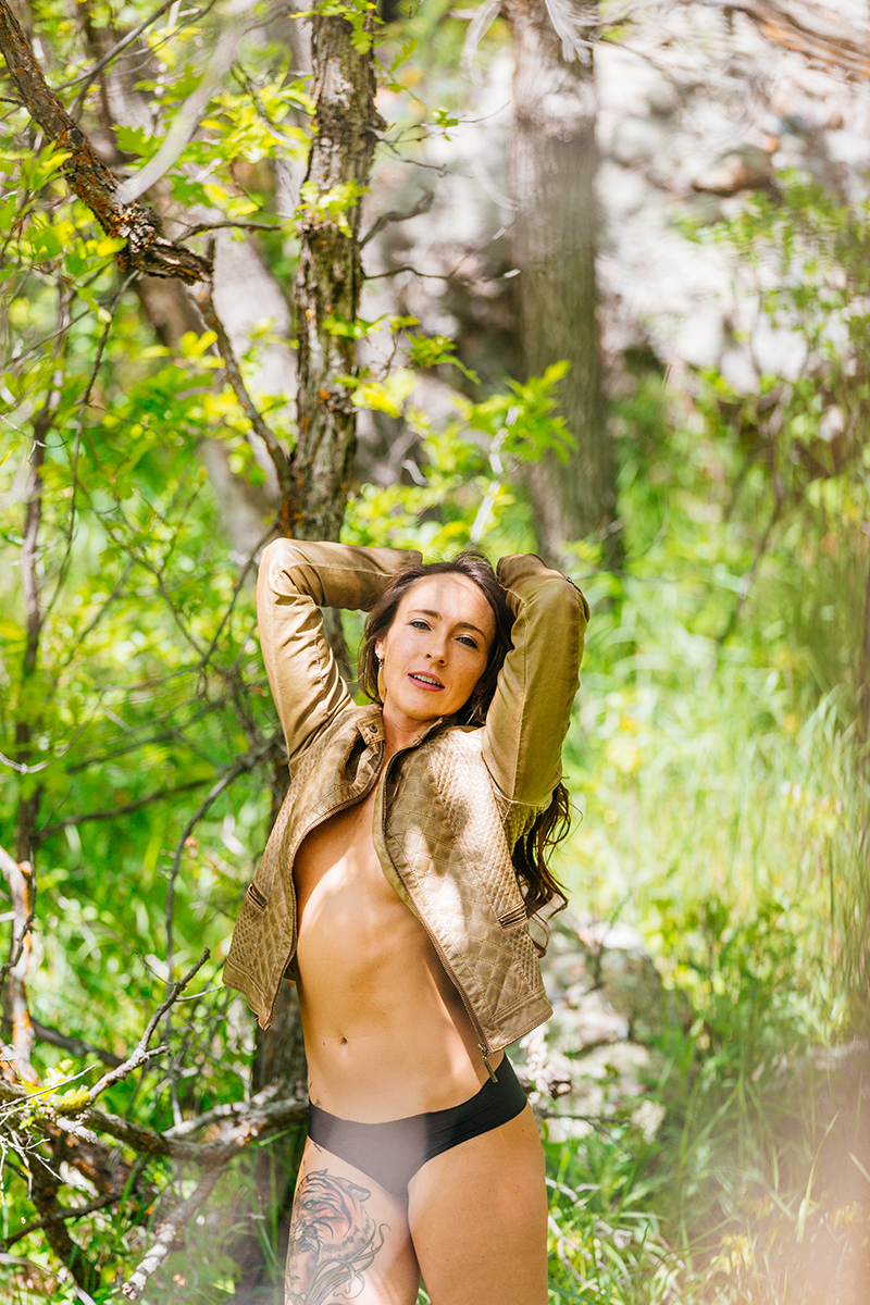 A beautiful young brunette woman poses topless for a Castlewood Canyon boudoir photography session wearing a tan leather jacket and black underwear standing in a forested area in Castle Rock, Colorado