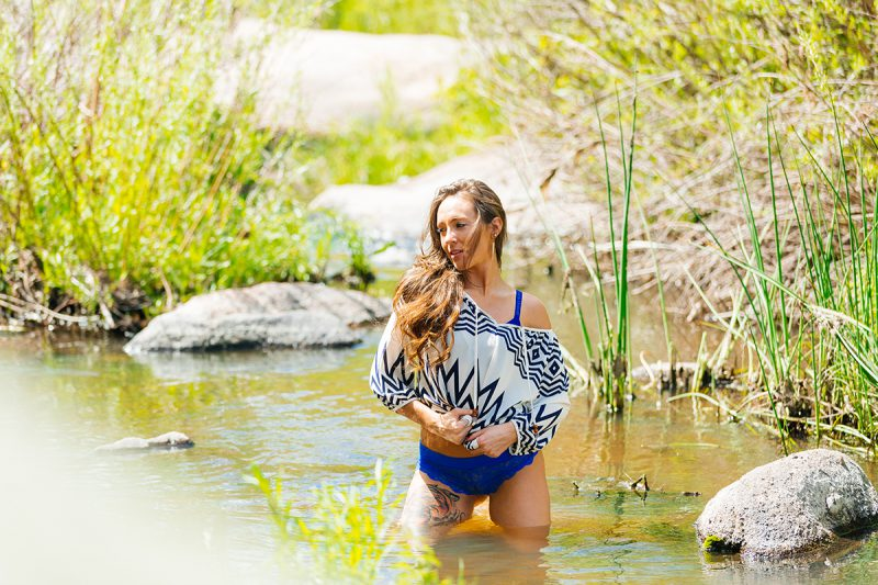 A beautiful young brunette woman poses for a Castlewood Canyon boudoir photography session wearing a white and blue chevron shirt and blue underwear sitting in a stream surrounded by bushes in Castle Rock, Colorado