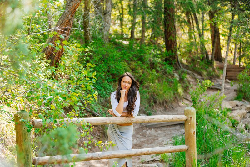 A beautiful young brunette woman poses for a Castlewood Canyon boudoir photography session wearing a gray dress leaning on a log rail in a forested area in Castle Rock, Colorado