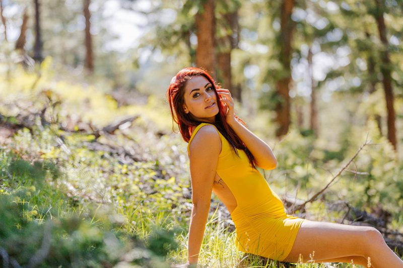 A beautiful young redheaded woman posing for a Genesee Park boudoir photography session wearing a yellow dress sitting on the side of a mountain in a forest in the Rocky Mountains near Denver, Colorado