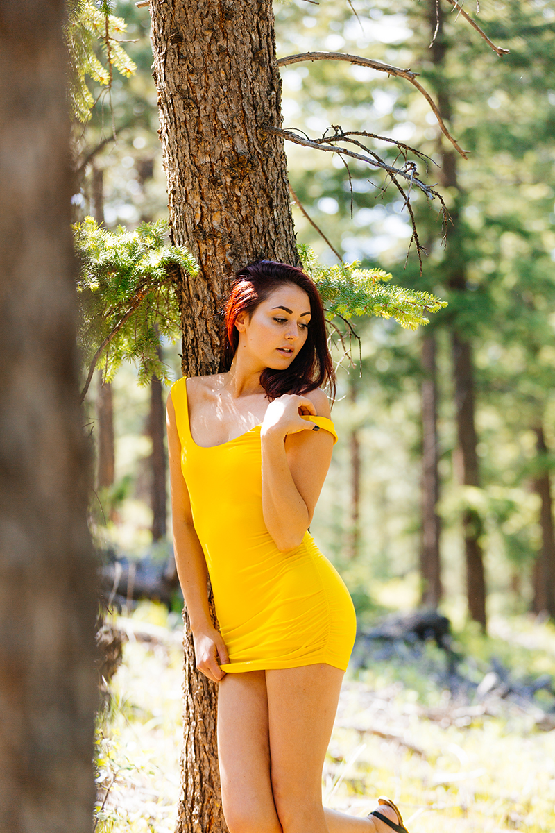 A beautiful young redheaded woman posing for a Genesee Park boudoir photography session wearing a yellow dress leaning against a tree on the side of a mountain in a forest in the Rocky Mountains near Denver, Colorado