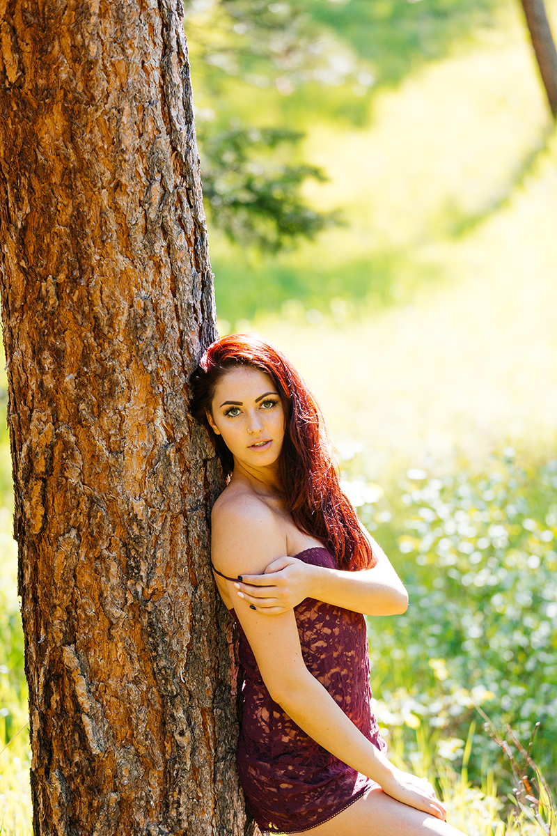 A beautiful young redheaded woman posing for a Genesee Park boudoir photography session wearing red lingerie leaning against a tree on the side of a mountain in a forest in the Rocky Mountains near Denver, Colorado