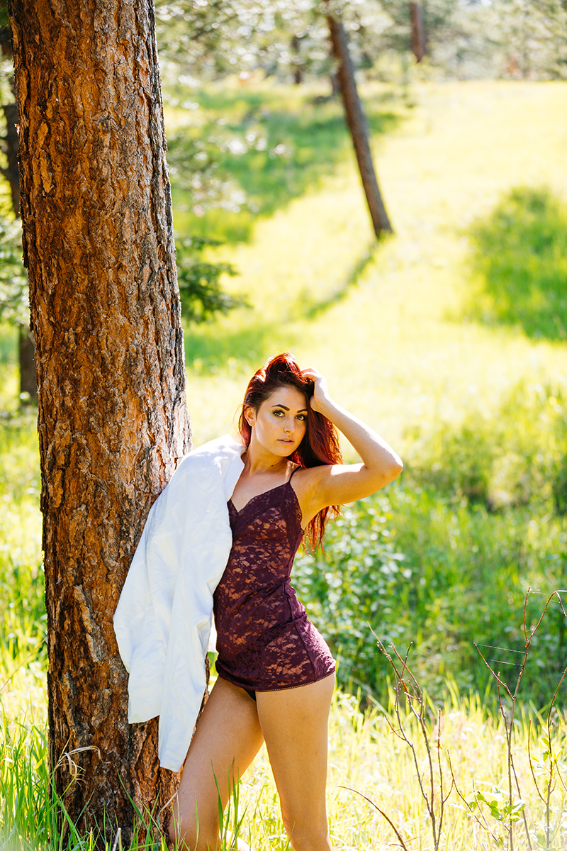 A beautiful young redheaded woman posing for a Genesee Park boudoir photography session wearing red lingerie and a white button up shirt leaning against a tree on the side of a mountain in a forest in the Rocky Mountains near Denver, Colorado