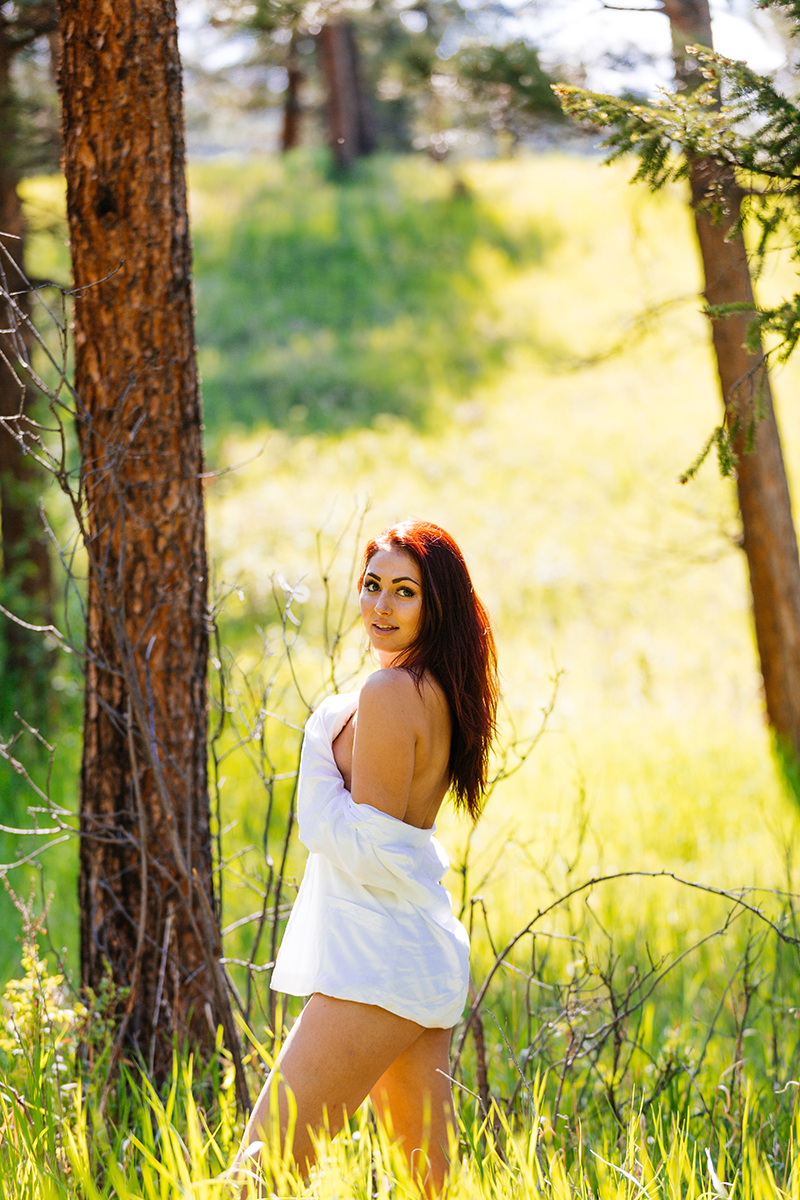 A beautiful young redheaded woman posing topless for a Genesee Park boudoir photography session wearing white underwear and a white button up shirt in a field on the side of a mountain in a forest in the Rocky Mountains near Denver, Colorado