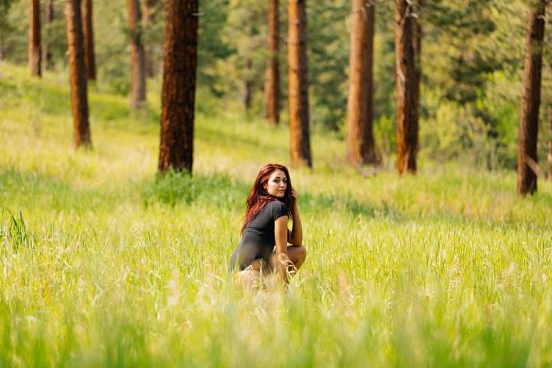 A beautiful young redheaded woman posing for a Genesee Park boudoir photography session wearing a black shirt and black underwear in a field on the side of a mountain in a forest in the Rocky Mountains near Denver, Colorado