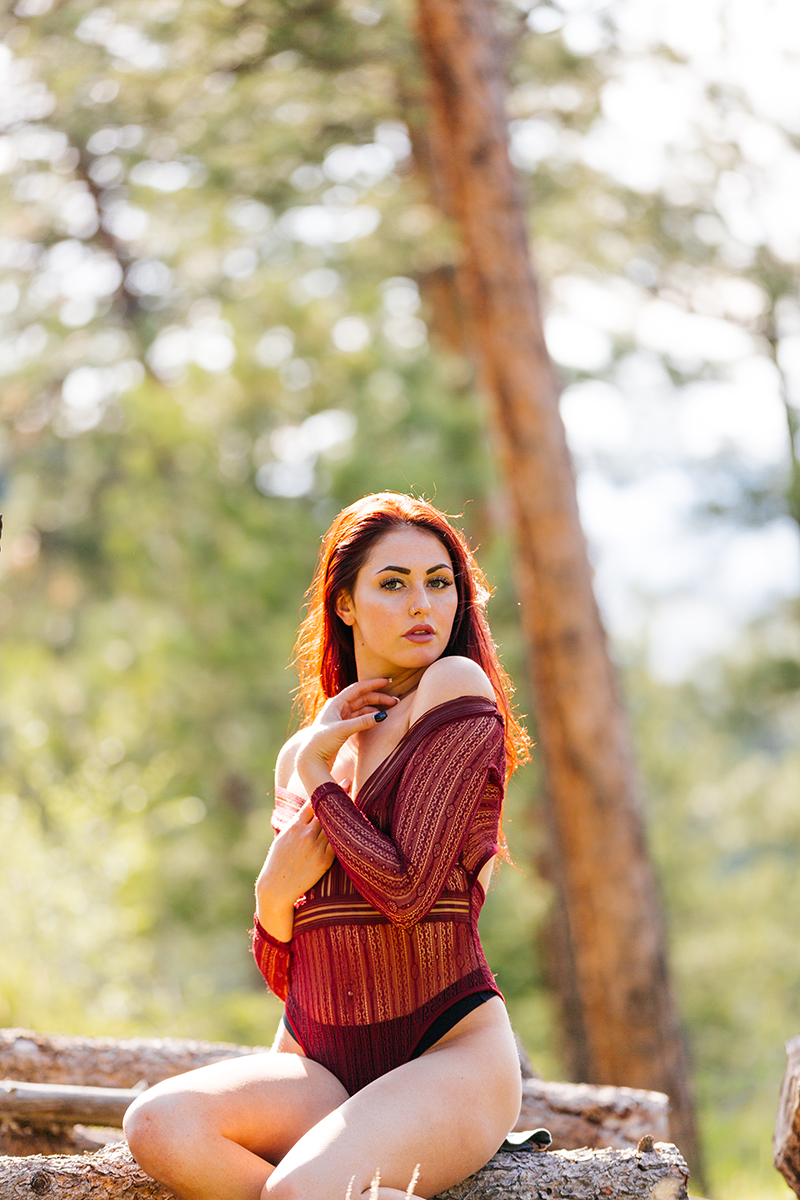 A beautiful young redheaded woman posing for a Genesee Park boudoir photography session wearing a red body suit lingerie and jean shorts sitting on a log in a field on the side of a mountain in a forest in the Rocky Mountains near Denver, Colorado