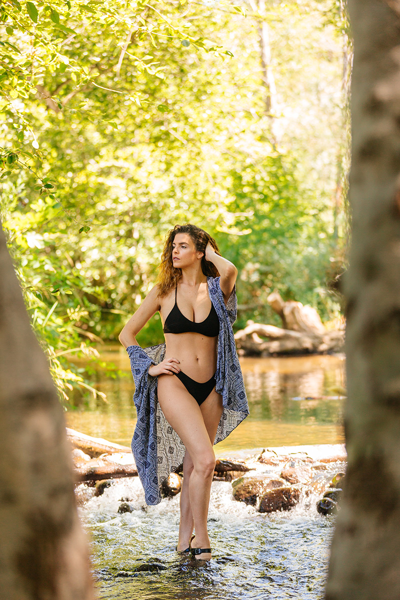 A beautiful brunette woman poses for a Miner's Ravine boudoir photography session wearing a black bikini and blue shawl standing in a creek in Roseville near Sacrament, California