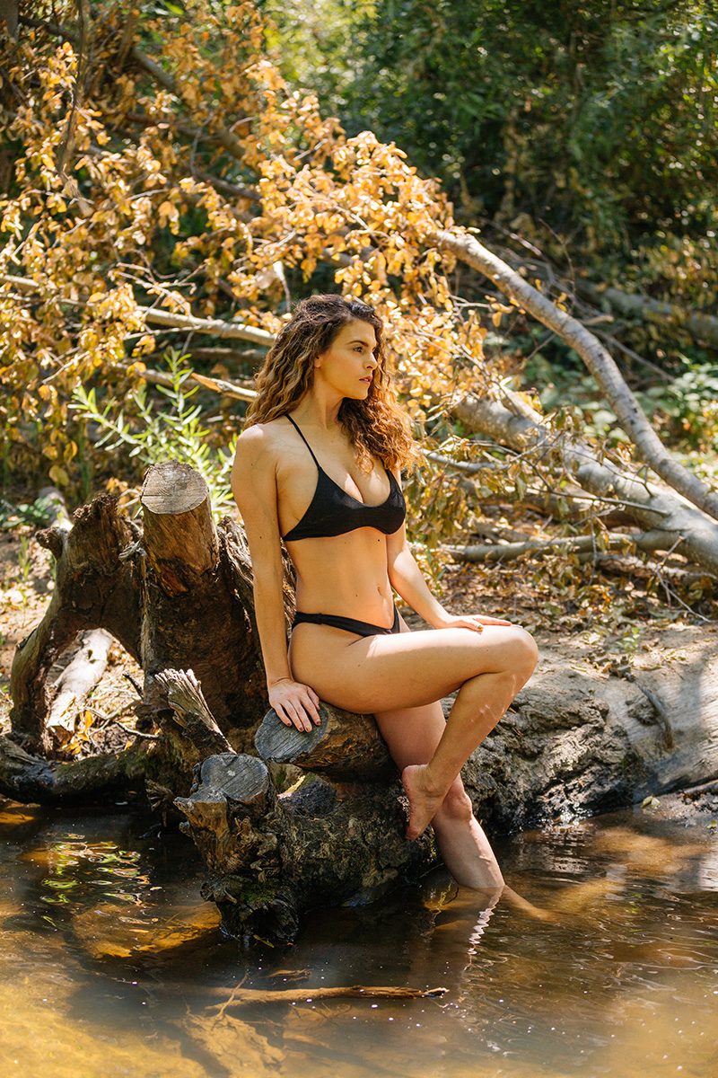 A beautiful brunette woman poses for a Miner's Ravine boudoir photography session wearing a black bikini sitting on a fallen tree in a creek in Roseville near Sacrament, California