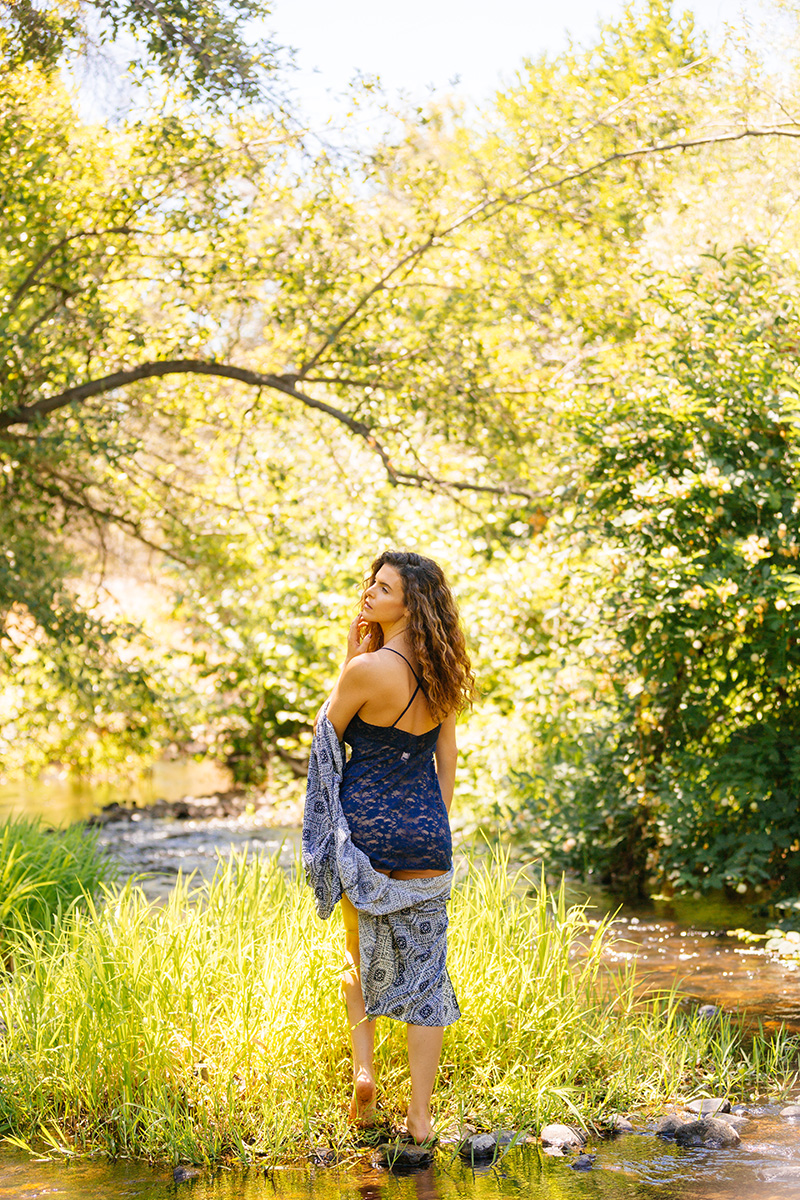 A beautiful brunette woman poses for a Miner's Ravine boudoir photography session wearing blue lingerie and a blue shawl in grass surrounded by the creek in Roseville near Sacrament, California