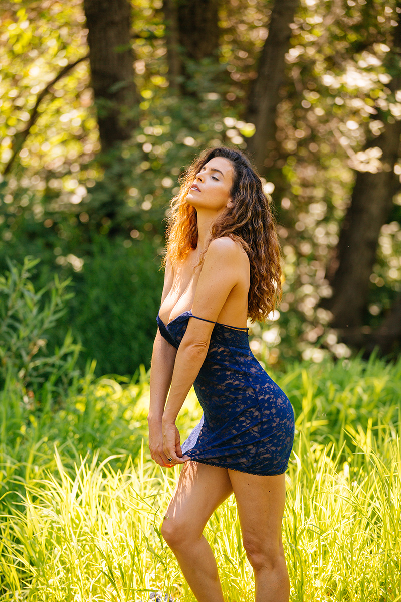 A beautiful brunette woman poses for a Miner's Ravine boudoir photography session wearing blue lingerie in grass surrounded by the creek in Roseville near Sacrament, California
