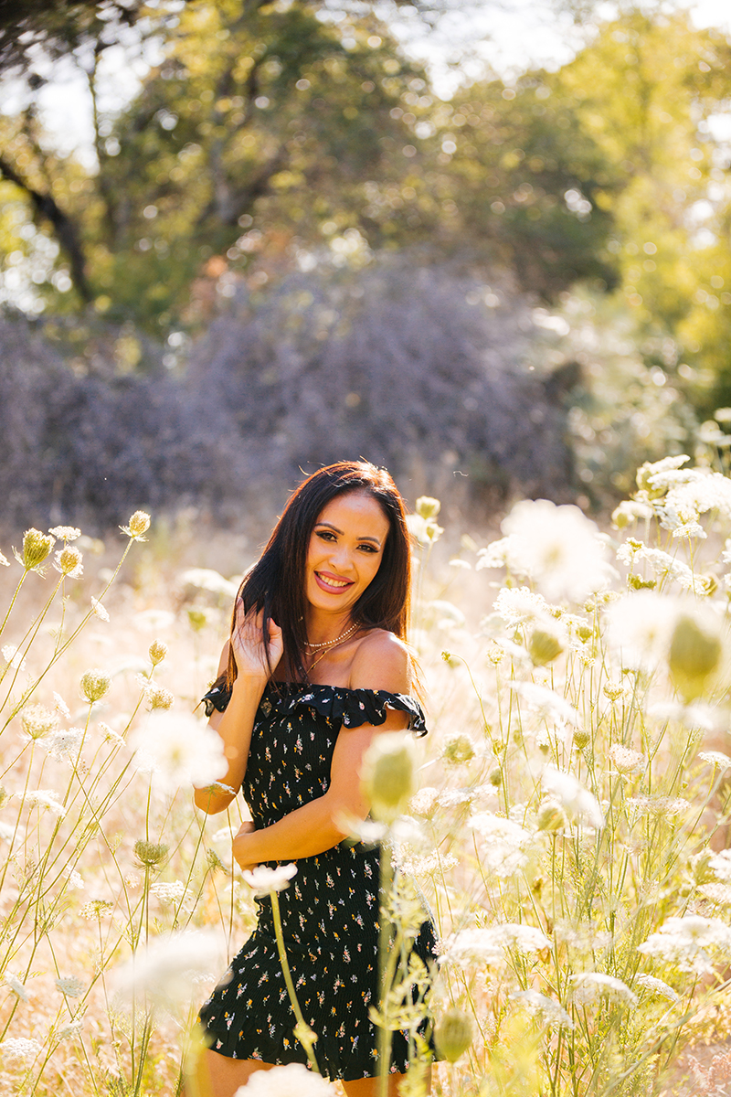 A beautiful brunette woman poses for a Secret Ravine fashion photography session in Roseville wearing a black dress in a field of flowers at sunset near Sacramento, California
