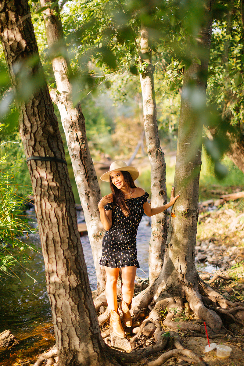 A beautiful brunette woman poses for a Secret Ravine fashion photography session in Roseville wearing a black dress and a straw hat in some trees next to a creek at sunset near Sacramento, California
