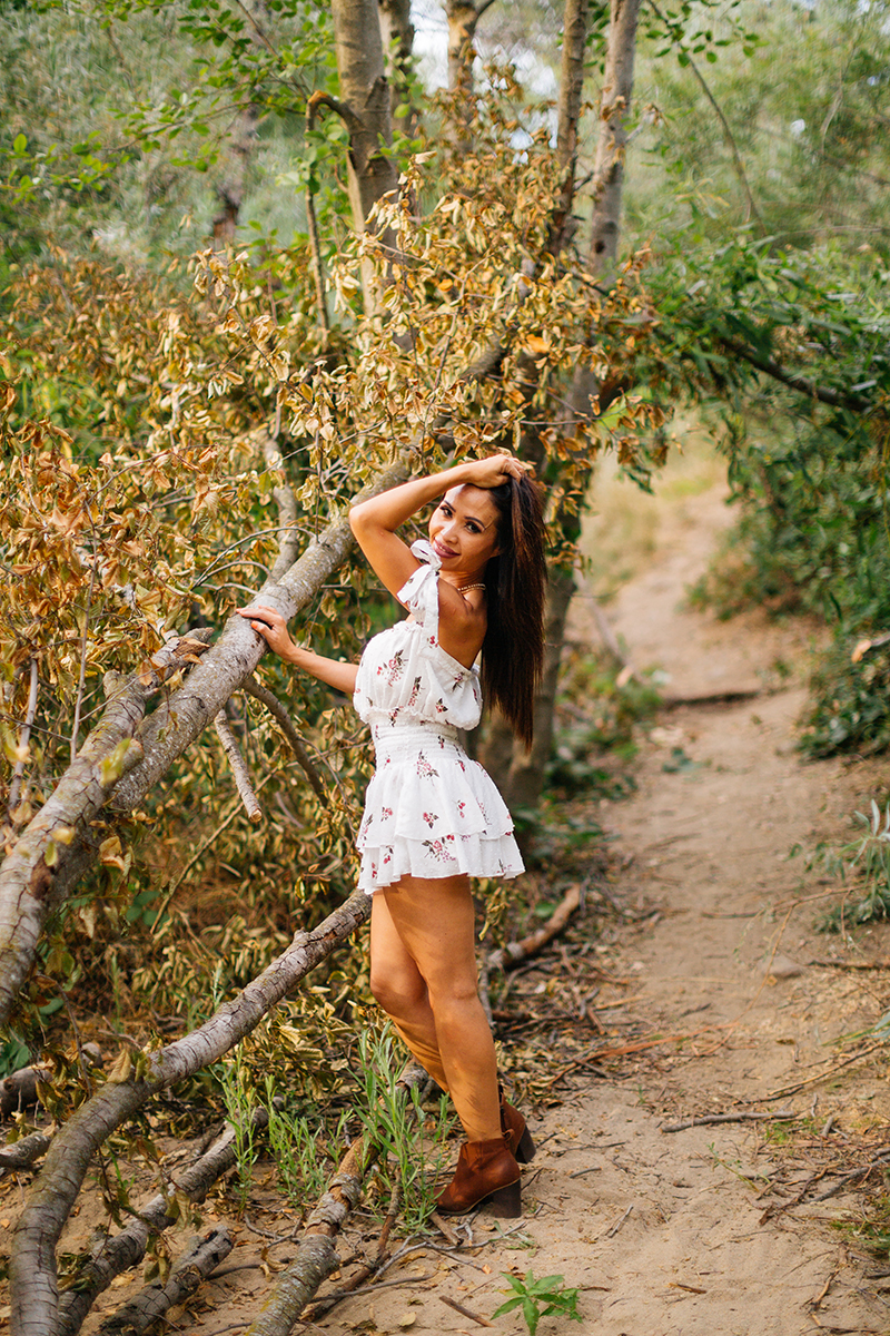 A beautiful brunette woman poses for a Secret Ravine fashion photography session in Roseville wearing a white dress in some trees at sunset near Sacramento, California