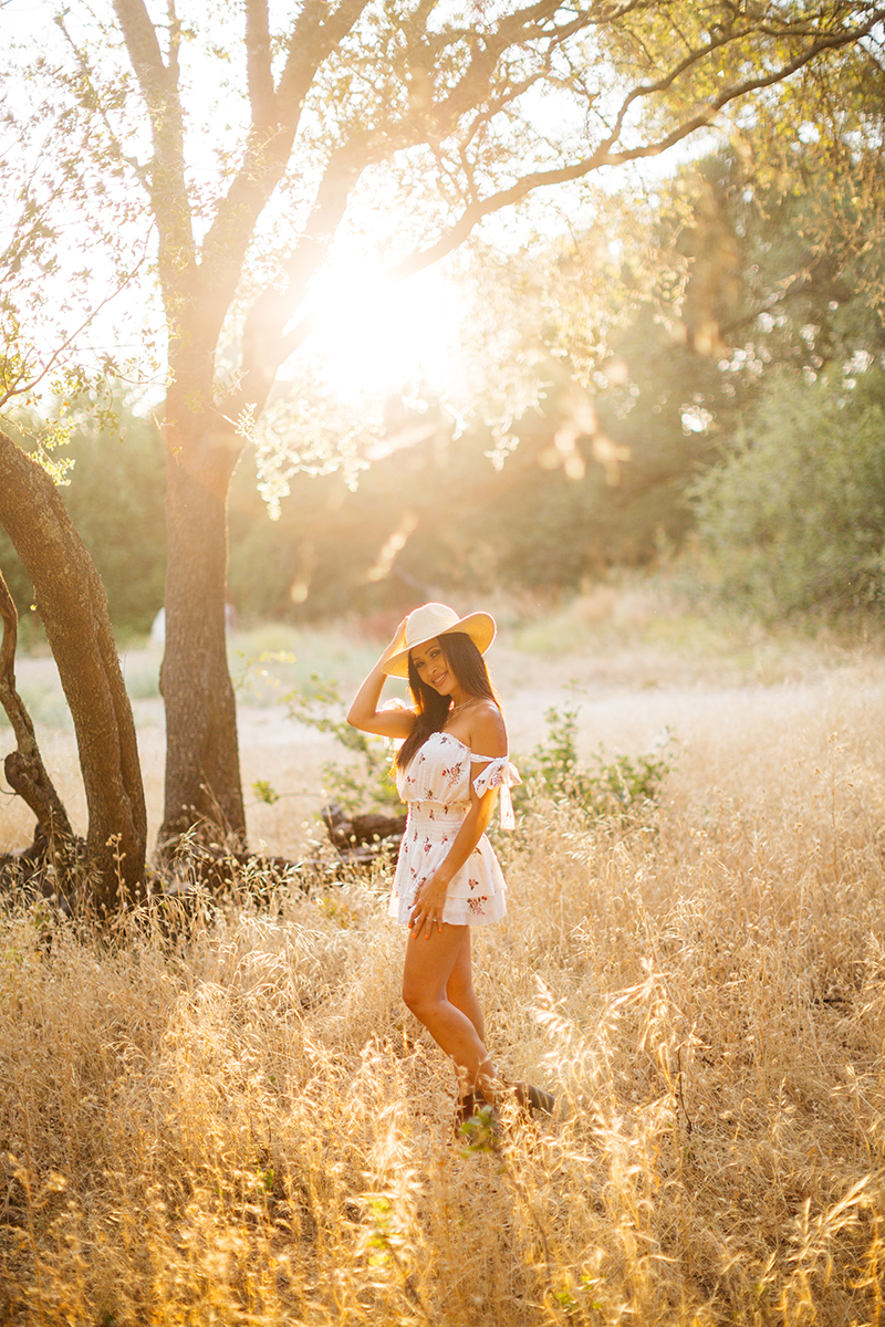 A beautiful brunette woman poses for a Secret Ravine fashion photography session in Roseville wearing a white dress and a straw hat in a field at sunset near Sacramento, California
