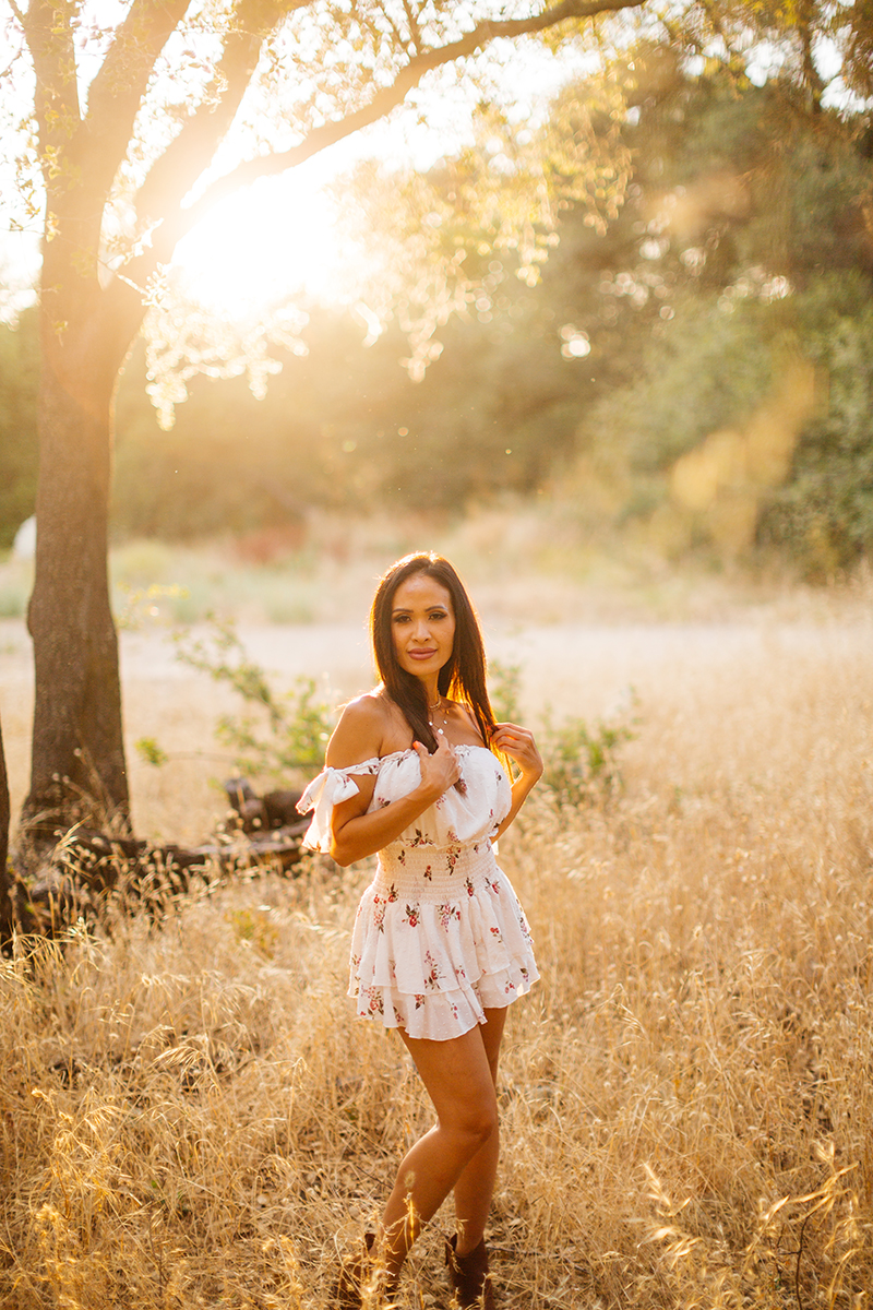 A beautiful brunette woman poses for a Secret Ravine fashion photography session in Roseville wearing a white dress in a field at sunset near Sacramento, California