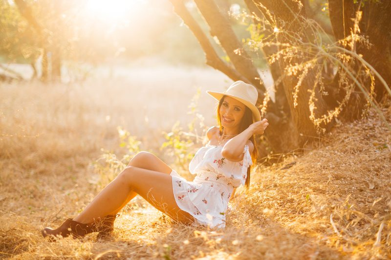 A beautiful brunette woman poses sitting for a Secret Ravine fashion photography session in Roseville wearing a white dress and a straw hat in a field at sunset near Sacramento, California