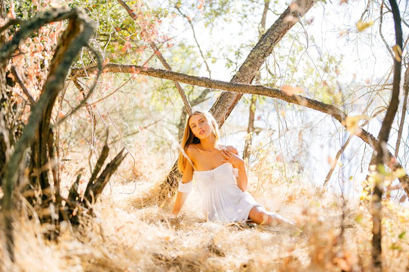 A beautiful young blonde woman sitting for a Rattlesnake Ramp fashion photography session wearing a white dress in a field surrounded by trees at Folsom Lake near Sacramento, California