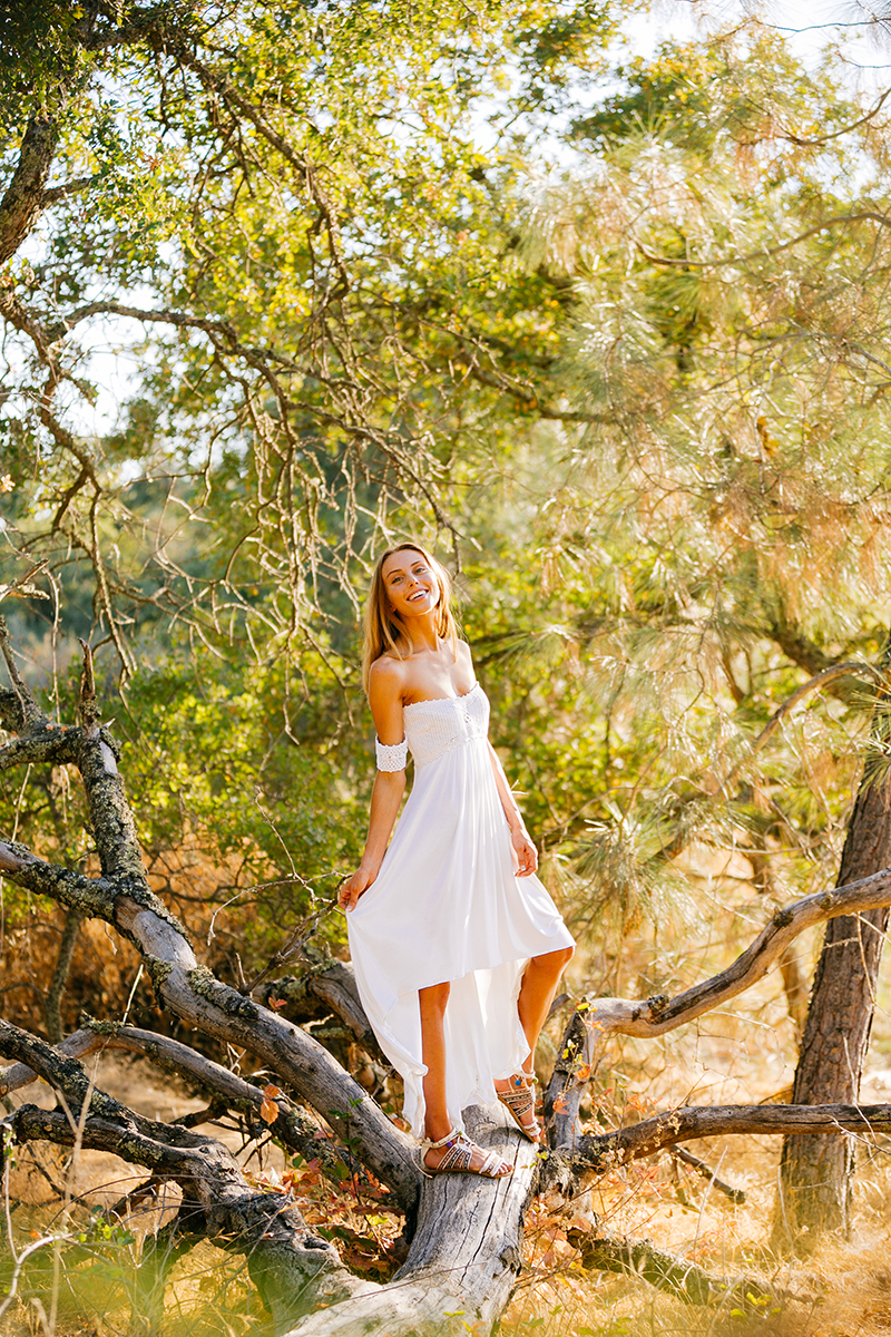 A beautiful young blonde woman posing for a Rattlesnake Ramp fashion photography session wearing a white dress in a field surrounded by trees at Folsom Lake near Sacramento, California