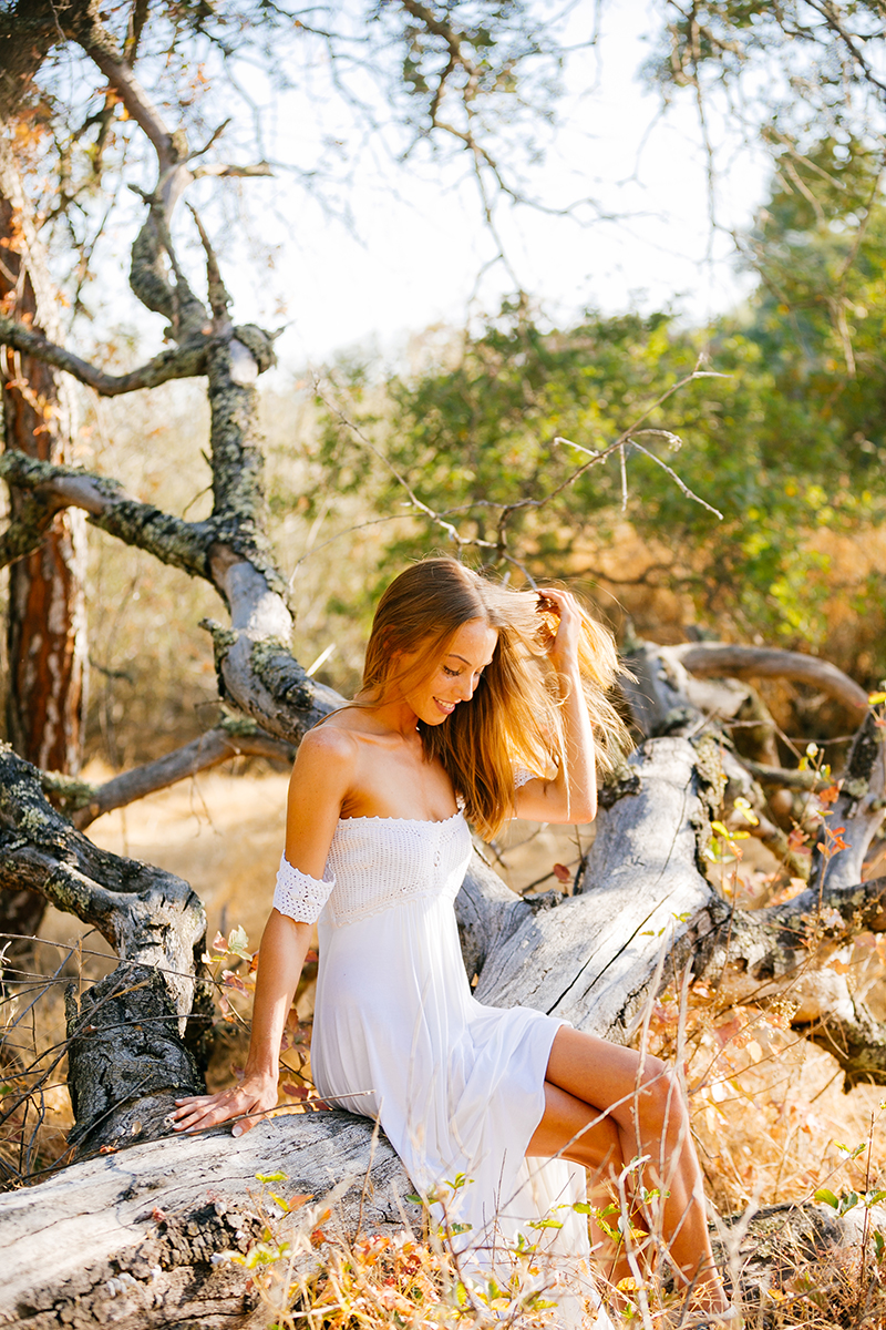 A beautiful young blonde woman sitting on a fallen tree for a Rattlesnake Ramp fashion photography session wearing a white dress in a field surrounded by trees at Folsom Lake near Sacramento, California