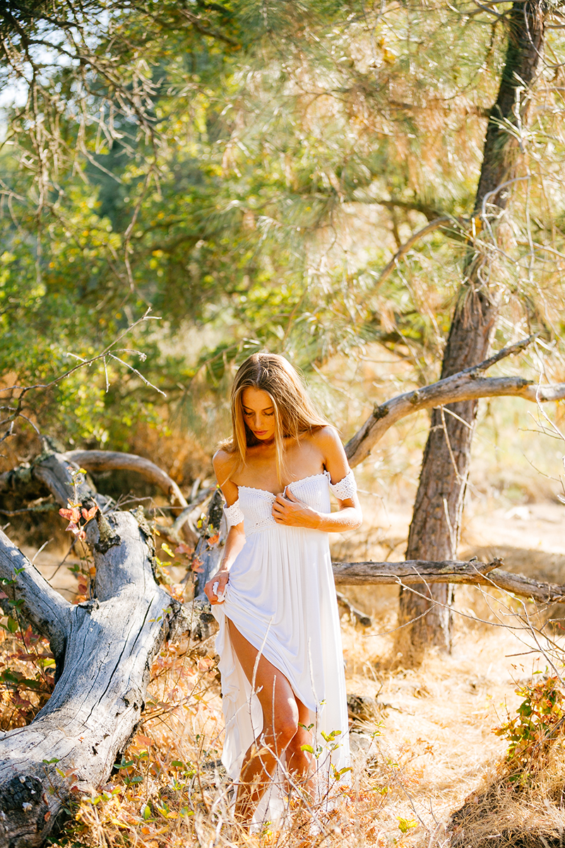 A beautiful young blonde woman standing near a fallen tree for a Rattlesnake Ramp fashion photography session wearing a white dress in a field surrounded by trees at Folsom Lake near Sacramento, California