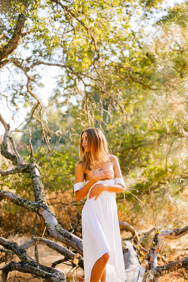 A beautiful young blonde woman standing topless near a fallen tree for a Rattlesnake Ramp fashion photography session wearing a white dress in a field surrounded by trees at Folsom Lake near Sacramento, California