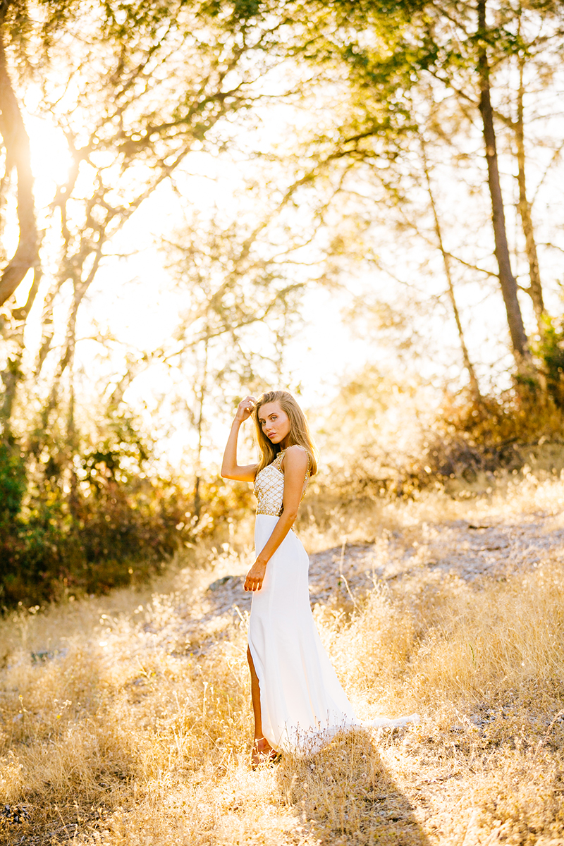 A beautiful young blonde woman poses for a Rattlesnake Ramp fashion photography session wearing a white and gold dress in a field surrounded by trees at Folsom Lake near Sacramento, California