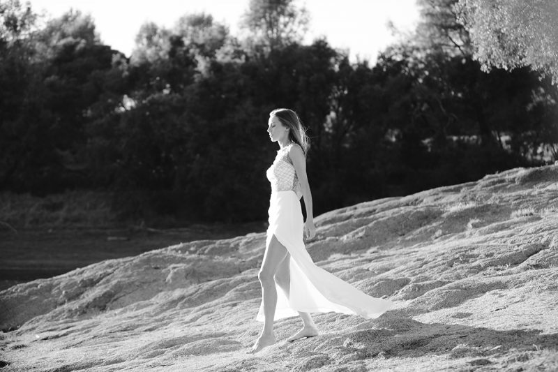A beautiful young blonde woman poses for a Rattlesnake Ramp fashion photography session wearing a white and gold dress on the shore near water at Folsom Lake near Sacramento, California