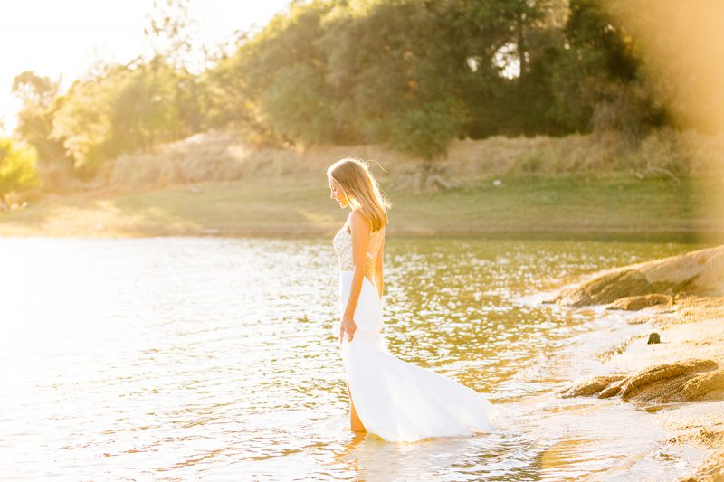 A beautiful young blonde woman poses for a Rattlesnake Ramp fashion photography session wearing a white and gold dress on the shore getting in the water at Folsom Lake near Sacramento, California