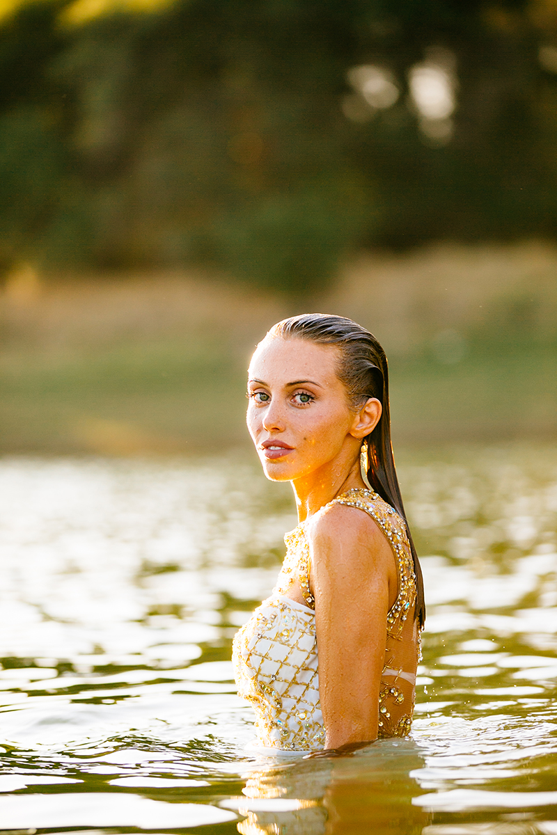 A beautiful young blonde woman poses for a Rattlesnake Ramp fashion photography session wearing a white and gold dress in the water at Folsom Lake near Sacramento, California