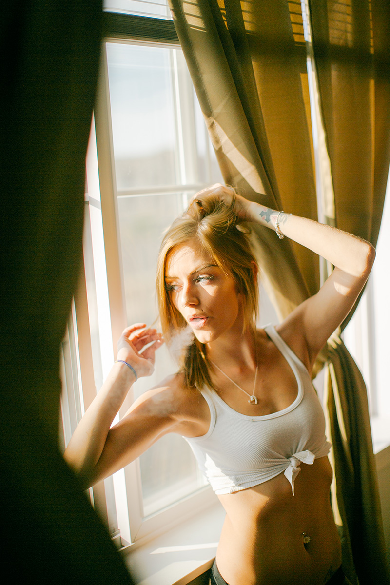 A beautiful young blonde woman poses in her bedroom for a Lafayette apartment boudoir photography session near Denver, CO wearing a white tank top and black underwear