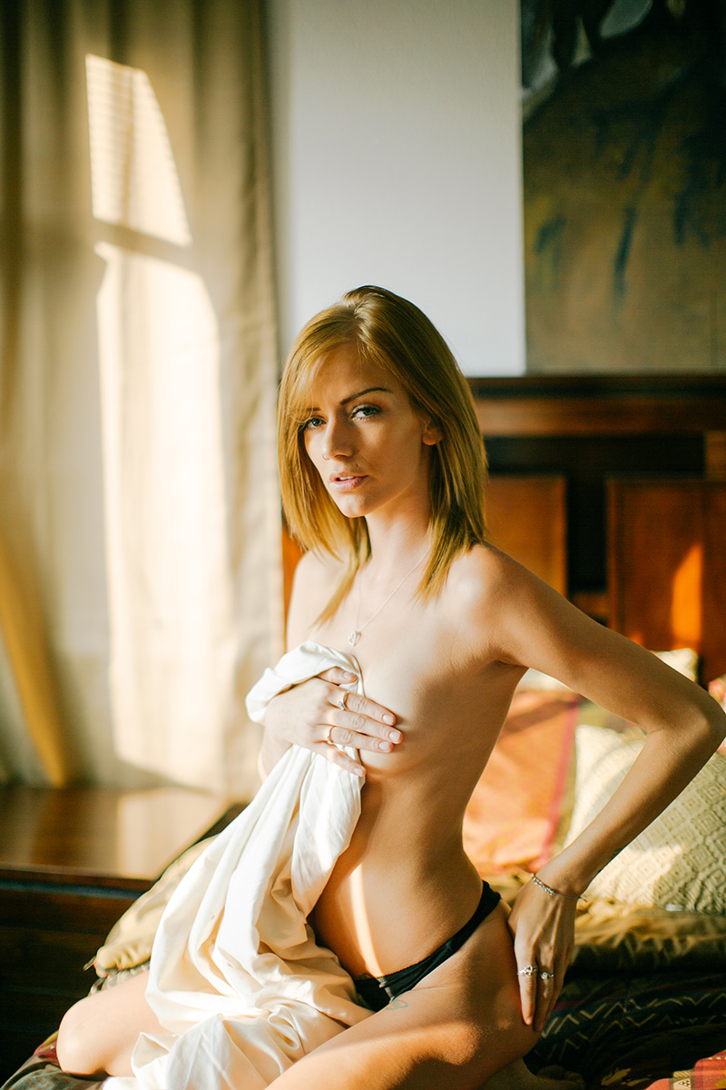 A beautiful young blonde woman poses topless on her bed in her bedroom for a Lafayette apartment boudoir photography session near Denver, CO wearing black underwear covering with a white sheet