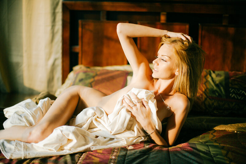 A beautiful young blonde woman poses nude on her bed in her bedroom for a Lafayette apartment boudoir photography session near Denver, CO covering with a white sheet