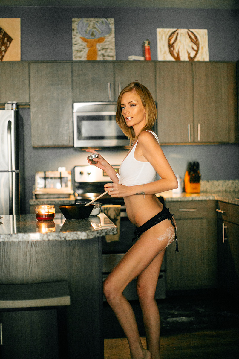 A beautiful young blonde woman poses in her kitchen for a Lafayette apartment boudoir photography session near Denver, CO wearing a white tank top and black underwear with flour hand prints on her butt