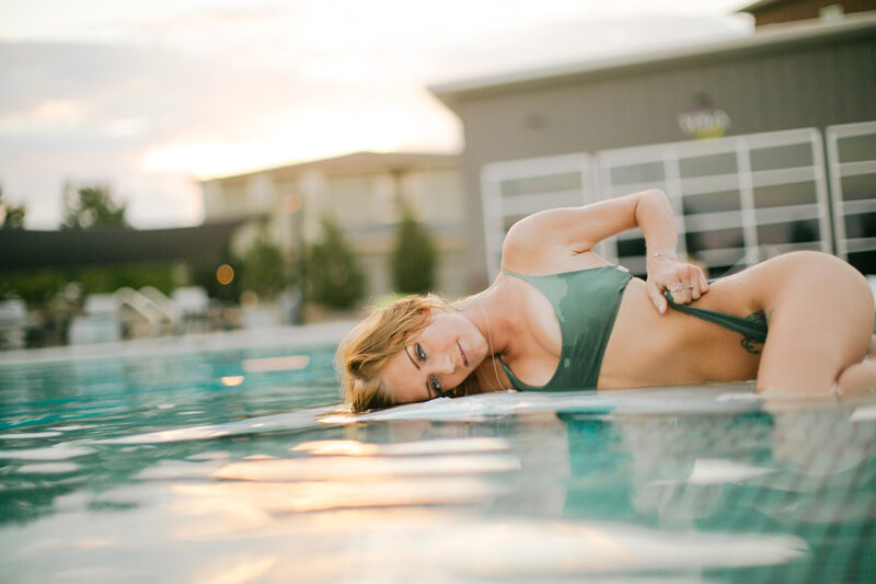 A beautiful young blonde woman lays in pool for a Lafayette apartment boudoir photography session near Denver, CO wearing a green swimsuit during the sunset