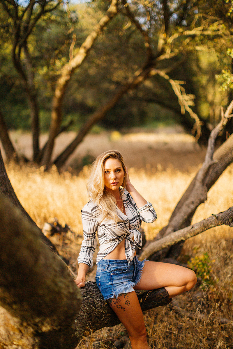 A beautiful blonde woman poses for a Secret Ravine boudoir photography session in Roseville wearing a plaid button up shirt, jean shorts and brown cowboy boots in a field leaning against a tree at sunset near Sacramento, California