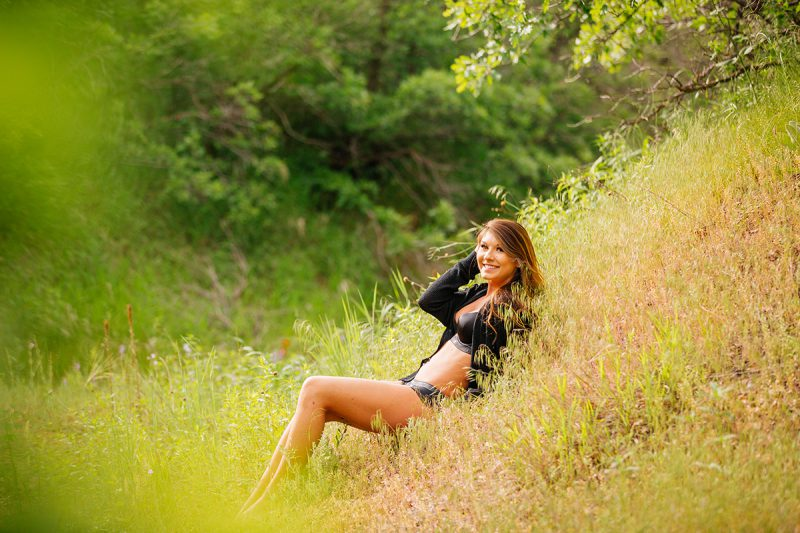 A beautiful young brunette poses for a Roxborough Park boudoir photography session wearing a black bra and underwear set with a black cardigan lying in grass on the side of a hill near Denver, Colorado