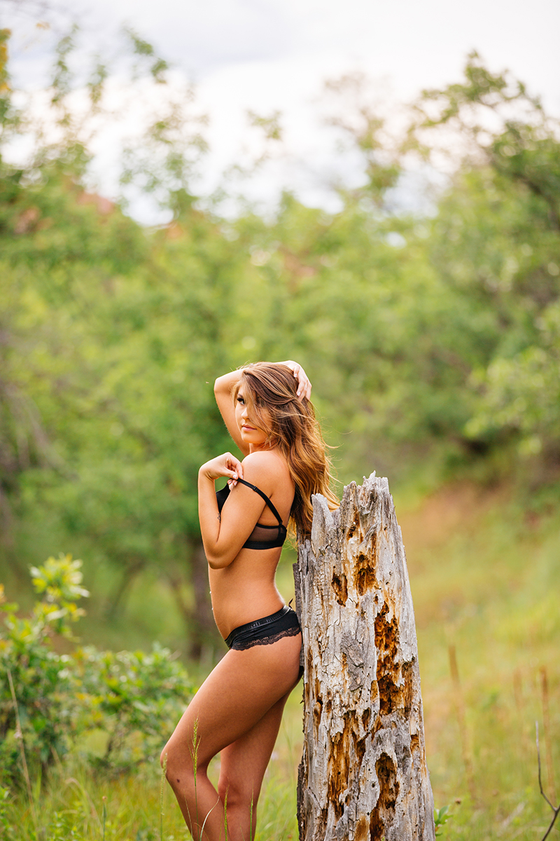 A beautiful young brunette poses for a Roxborough Park boudoir photography session wearing a black bra and underwear set next to a dead tree stump near Denver, Colorado