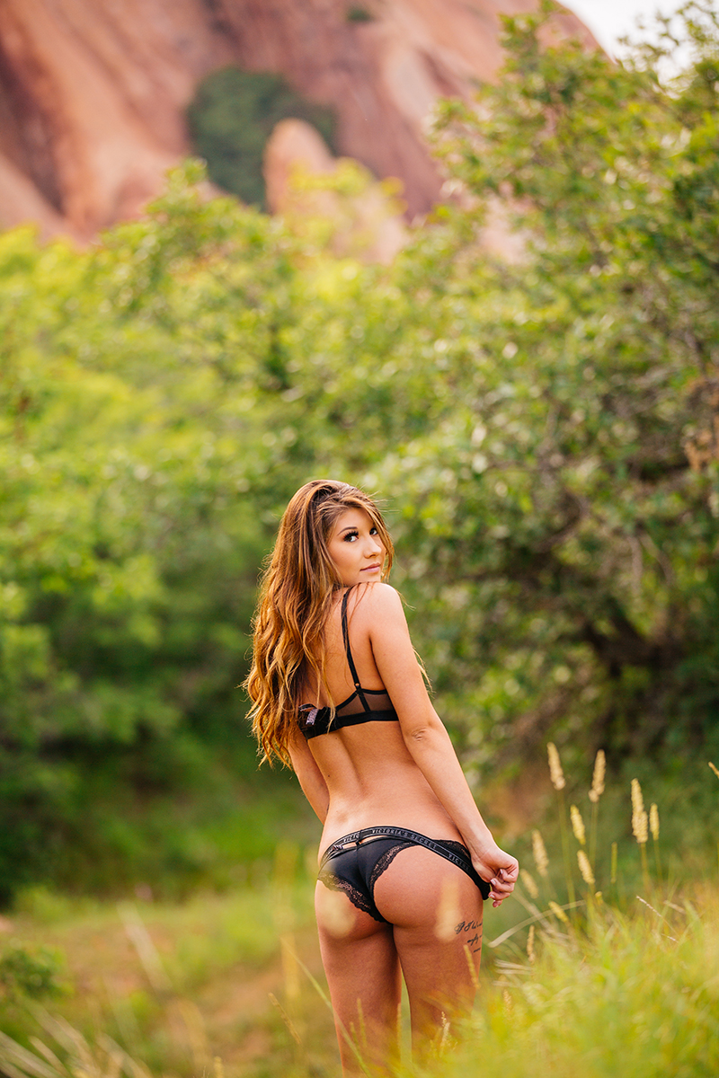 A beautiful young brunette poses for a Roxborough Park boudoir photography session wearing a black bra and underwear set in a field with the red rock formations in the background near Denver, Colorado