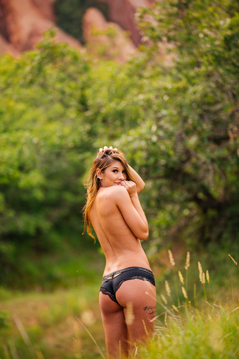 A beautiful young brunette poses topless for a Roxborough Park boudoir photography session wearing black underwear in a field with the red rock formations in the background near Denver, Colorado