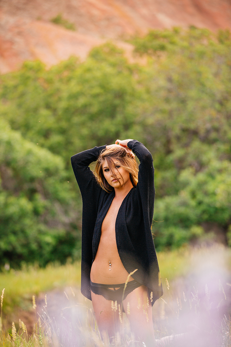 A beautiful young brunette poses topless for a Roxborough Park boudoir photography session wearing a black cardigan and black underwear in a field with the red rock formations in the background near Denver, Colorado