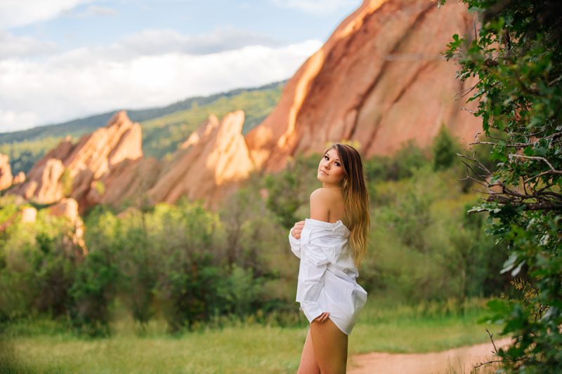 A beautiful young brunette poses topless for a Roxborough Park boudoir photography session wearing a black underwear and a white button up shirt in a field with the red rock formations in the background near Denver, Colorado