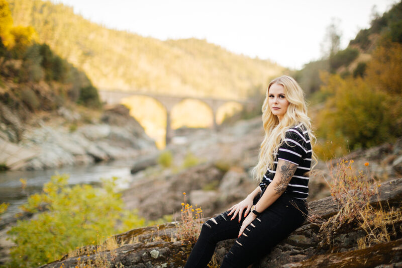 A beautiful young blonde woman poses for an Auburn boudoir photography near the North Fork American River sitting on a rock wearing black ripped jeans and a black striped shirt.